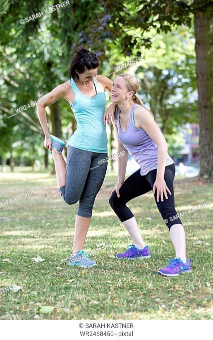 Two women stretch, warm up