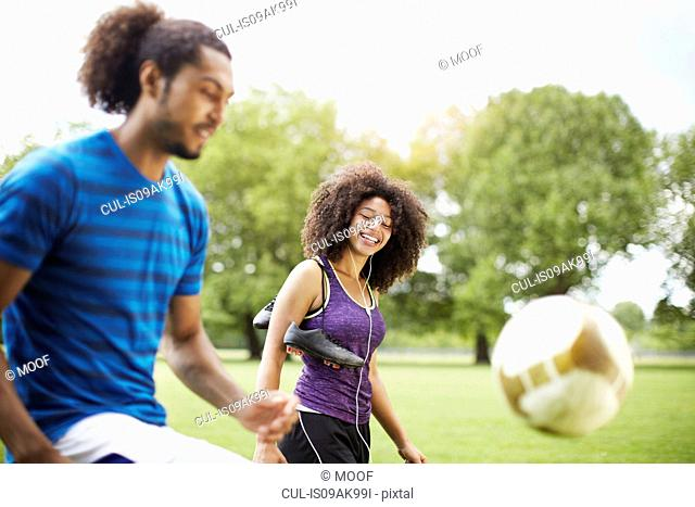 Young soccer couple playing keepy uppy in park