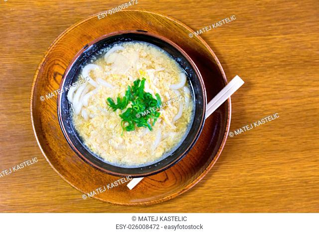Miso Ramen Asian noodles with egg and parsley in wooden bowl on brown rustic background