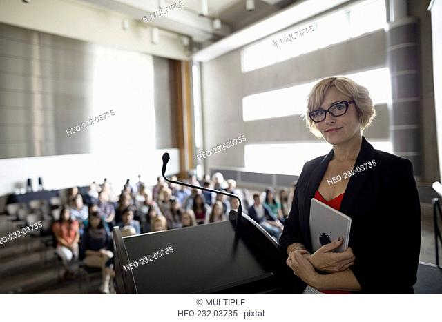 Portrait confident professor at podium in auditorium