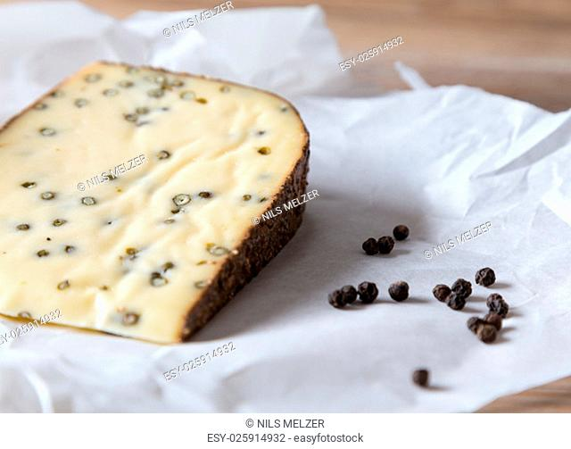 pepper cheese and peppercorns on a wooden table