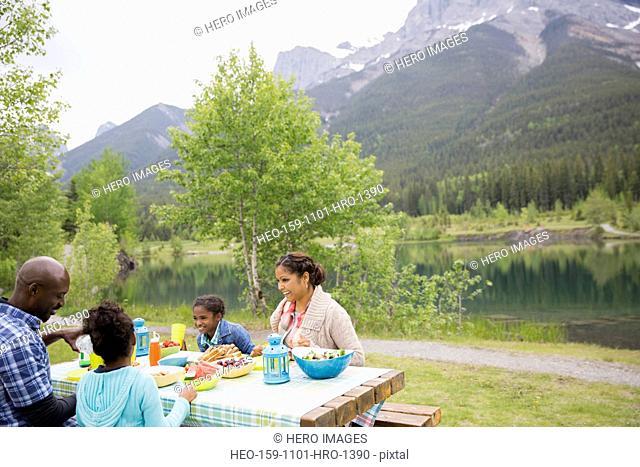 Family eating at picnic table near lake