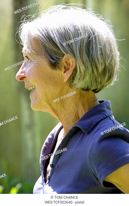 Germany, Bavaria, Senior woman looking away, smiling