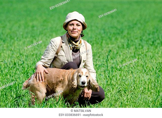 Travel woman with hat and backpack on the green field with grass and trees and a cocker spaniel dog