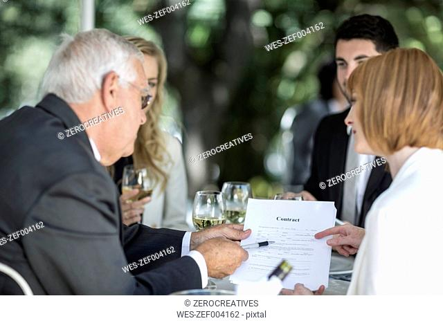 Elegant people at outside restaurant discussing a contract