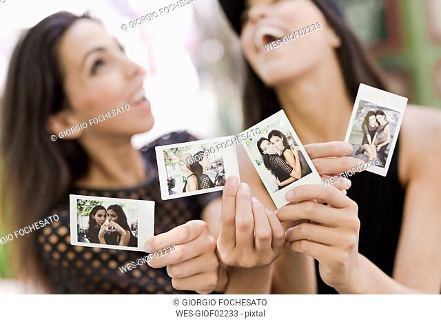 Two happy twin sisters holding instant photos of themselves
