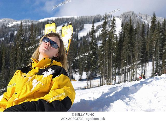 A young women rests on her skis at Sun Peaks Ski Resort, just North of Kamloops, British Columbia, Canada