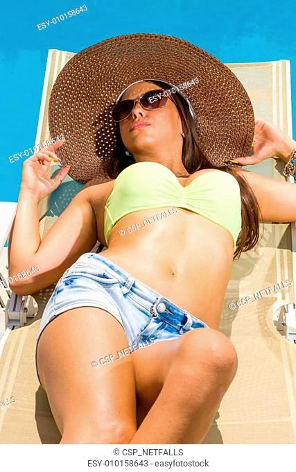Beautiful woman relaxing on lounger in hotel