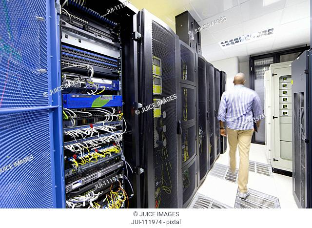 Technician with digital tablet walking away from camera in server data centre