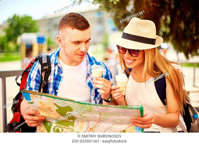 Happy tourists with ice-cream consulting guide in foreign city