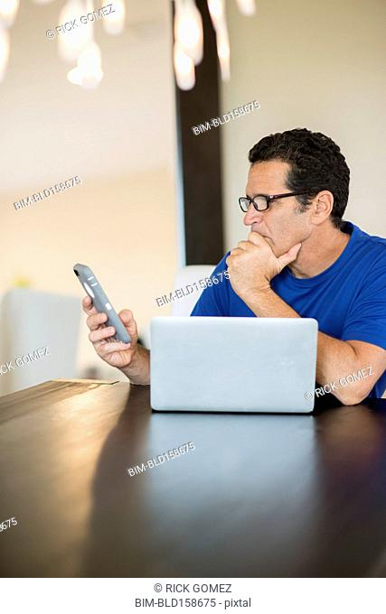 Hispanic man at laptop using cell phone at table