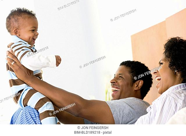 African parents playing with son in bed