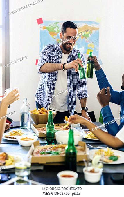 Group of friends clinking beer bottles at dining table