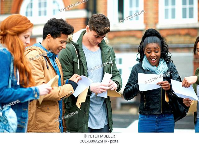 Young adult college students reading exam results on campus