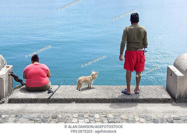 Couple with their dog fishing from sea wall in Las Palmas, Gran Canaria, Canary Islands