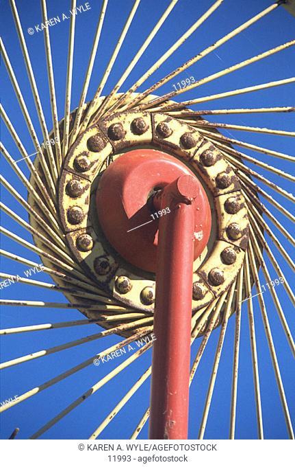 Hay rake, sunlit against deep blue sky