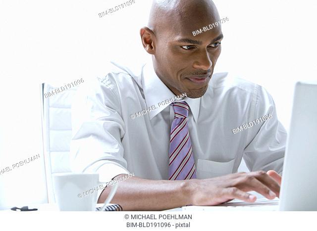 Mixed race businessman using laptop at desk