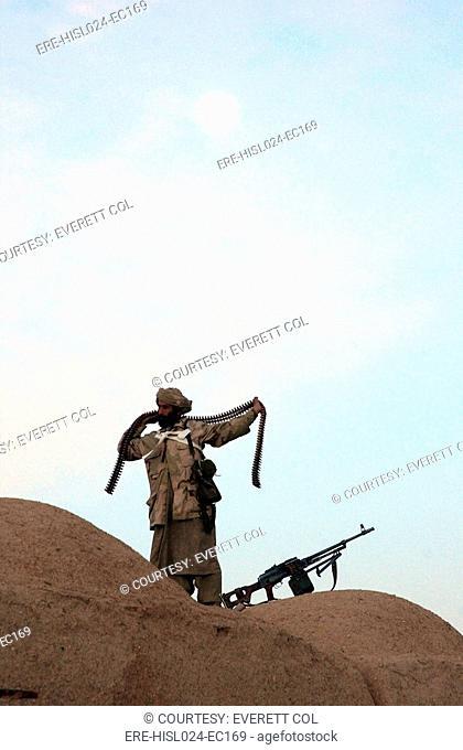 An Anti-Taliban fighter wraps a bandolier of Kalashnikov machine gun ammunition around his body. Helmand Province Jan.1 2002