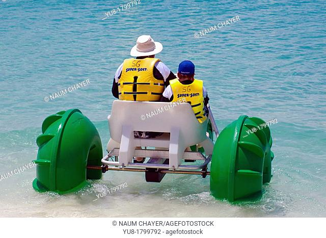 Old man and boy go for a sea cycle ride, Georgetown, Grand Cayman, Central America, Western Caribbean