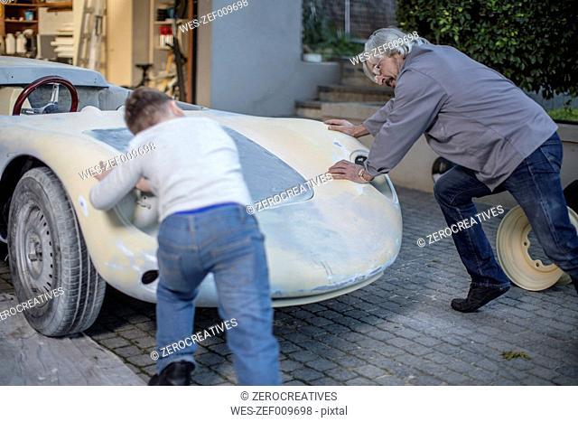 Senior man and boy pushing old car back in garage