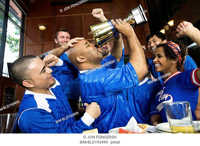 Cheering teammates and man drinking from trophy
