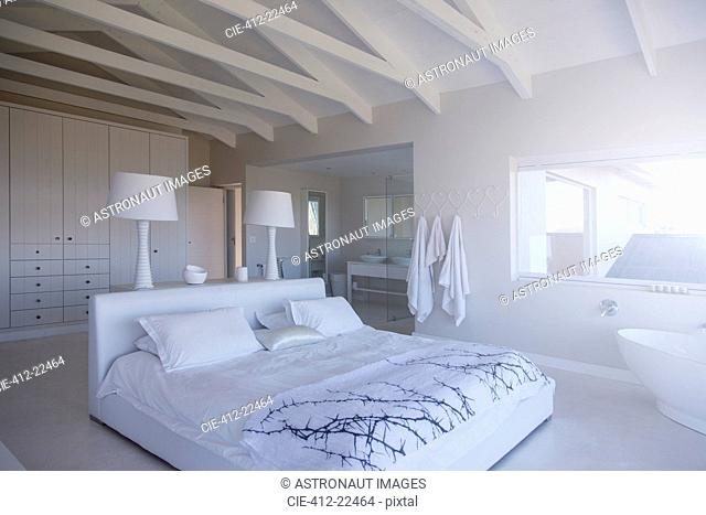 Modern white bedroom interior with double bed and bathtub