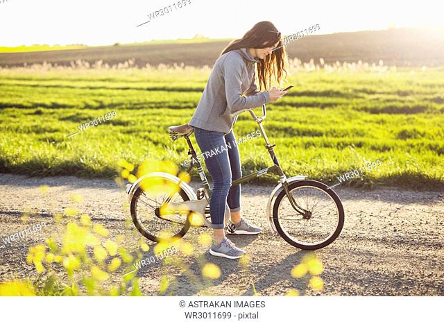 Woman texting on mobile phone during bicycle trip