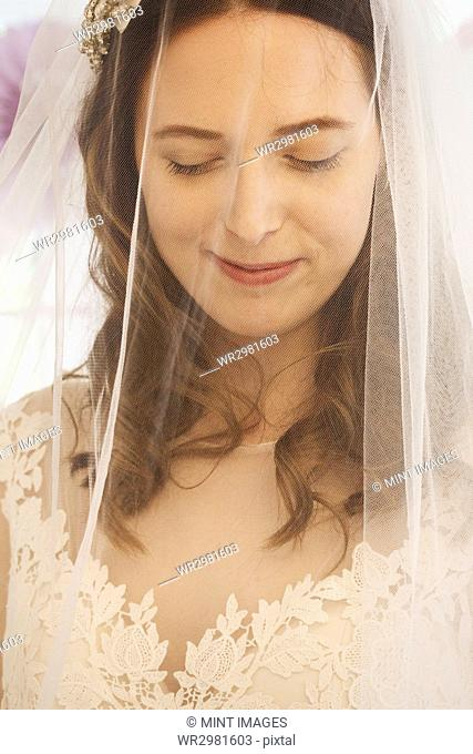 A young woman, a bride in a wedding dress with lace bodice, and a net veil over her face
