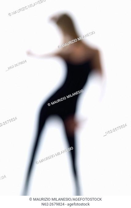 Blurred silhouette of a woman, she dances on a white backdrop