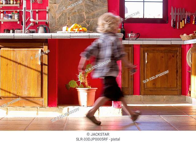 Boy running in kitchen