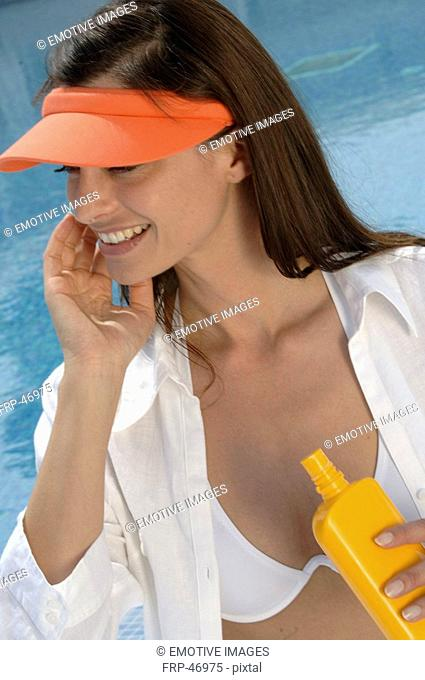 Woman at the swimming pool is applying sunlotion