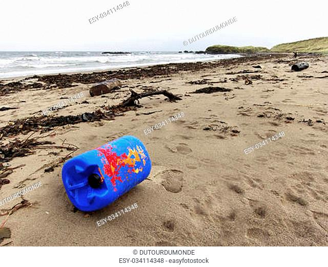 A blue and red plastic drum on a beach, pollution concept