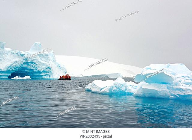 Group of people crossing the ocean in the Antarctic in a rubber boat, icebergs in the background
