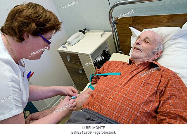 Photo essay at the department of dermatology at the Bocage hospital, University Hopital of Dijon, France. The nurse taking blood sample on a 72-year-old patient