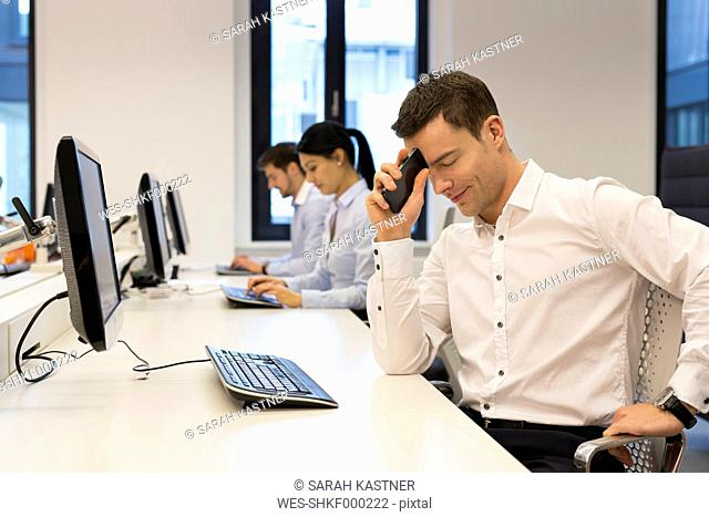 Frustrated man at desk with colleagues in background