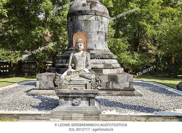 Seated Buddha image with the hand position of Bhumisparsha mudra in the garden of Mendut Buddhist Monastery. Magelang Regency, Java, Indonesia