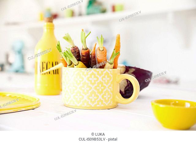Cup of fresh colourful carrots on kitchen table