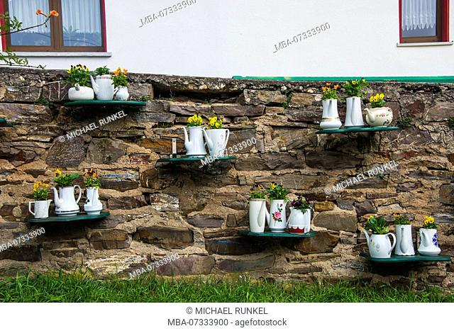 Coffeepots as flower vases on a wall in Cochem, Moselle valley, Rhineland-Palatinate, Germany
