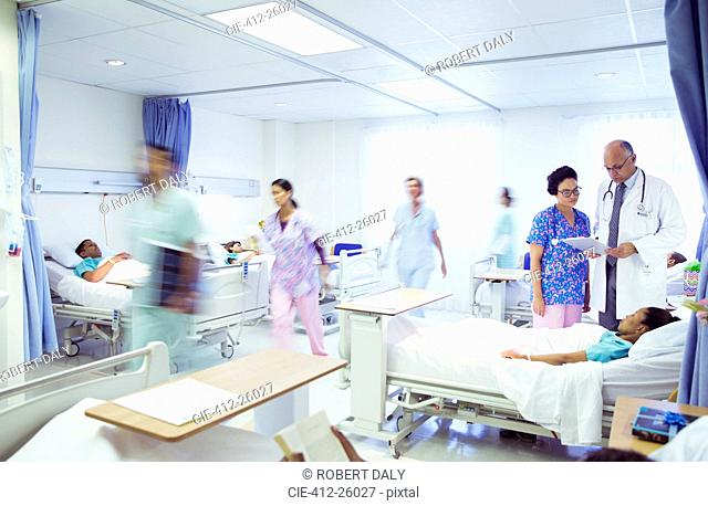 Doctors and nurses making rounds in hospital room