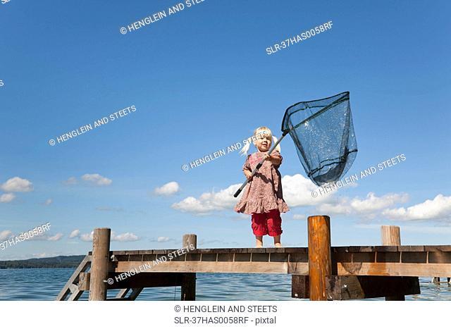 Girl fishing with net in lake