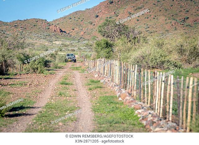 A vehicle driving up a dirt path on the property of Dabis Guest Farm in Helmeringhausen, southern Namibia, Africa