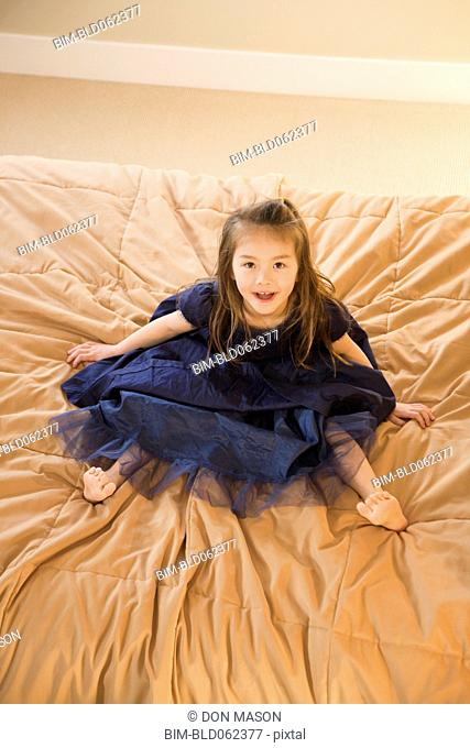 Mixed race girl in dress on bed