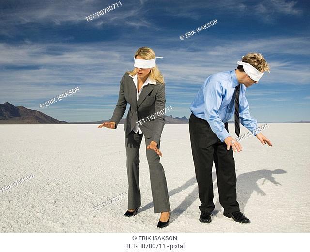 Blindfolded businesspeople on salt flats, Salt Flats, Utah, United States