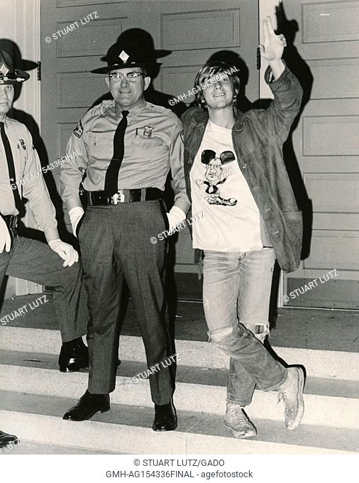 A student wearing hippie attire stands with a Sheriff's deputy and flashes a peace sign hand gesture during an anti Vietnam War student sit-in protest at North...