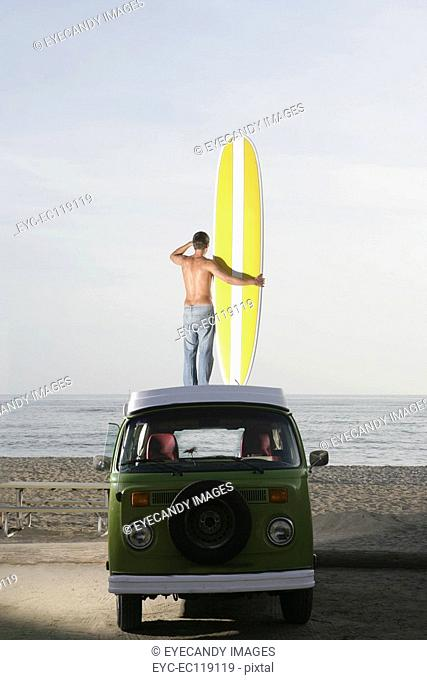 Young man with surfboard on roof of van