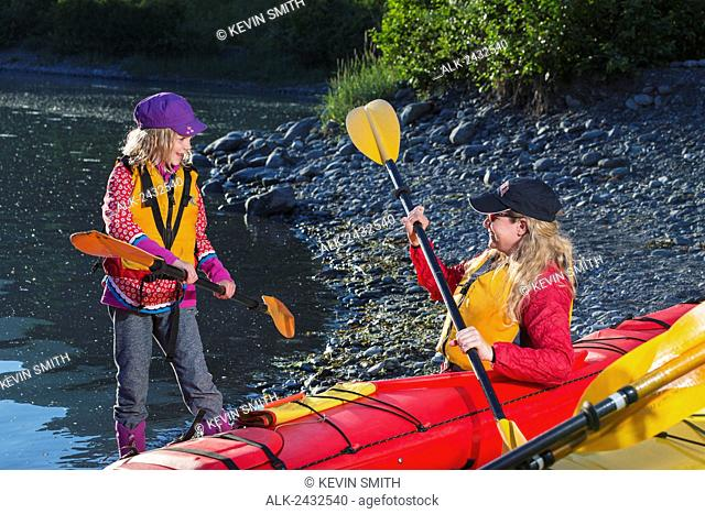 Middle aged woman in a kayak on the shore with a young girl, Shoup Bay State Marine Park, Prince William Sound, Valdez, Southcentral Alaska