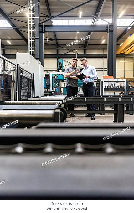 Two men with clipboard talking on factory shop floor