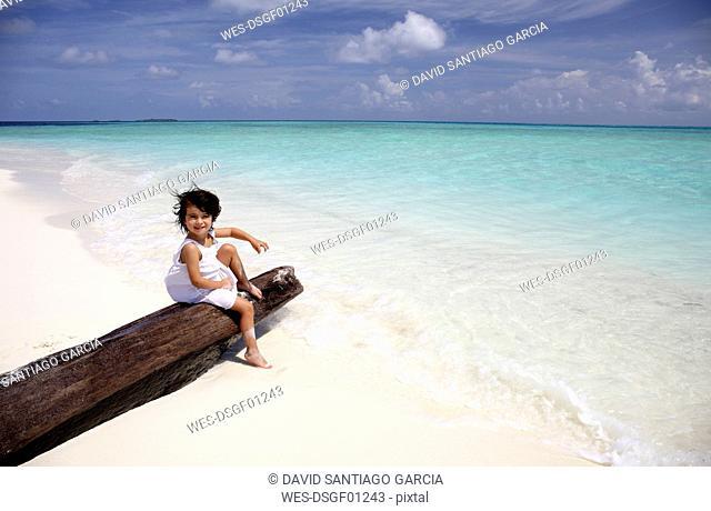 Maldives, girl sitting on a log on a beach