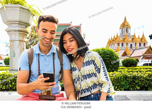 Young tourist couple looking at smartphone outside temple, Bangkok, Thailand