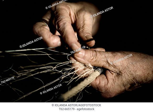 Woman's hand working on fishing net. Costa Dorada, Tarragona province, Catalonia, Spain